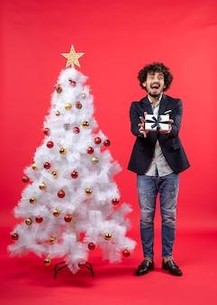 Schockierter junger mann, der sein geschenk zeigt, das nahe geschmücktem weißem weihnachtsbaum auf der rechten seite von rot steht