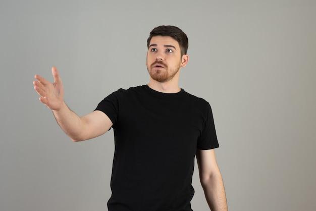Schockierter junger mann, der seine hand hochhält und scheint erschrocken zu sein.