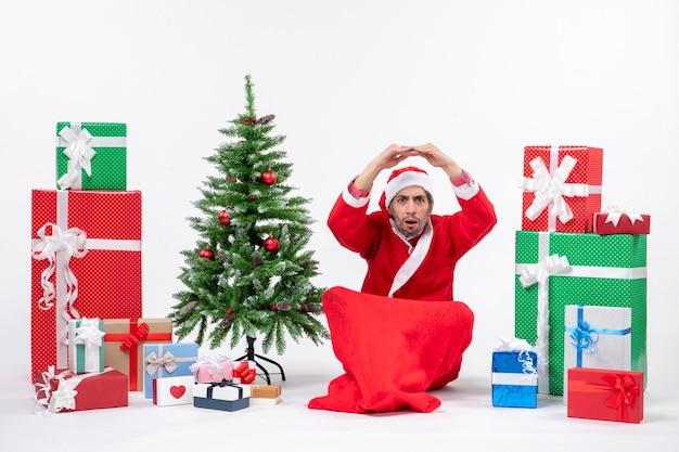 Schockierter junger mann feiern neujahrs- oder weihnachtsfeiertag, der auf dem boden nahe geschenken und geschmücktem weihnachtsbaum sitzt