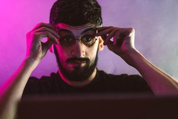 Schockierter junger mann in der brille, die auf einem laptopbildschirm schaut