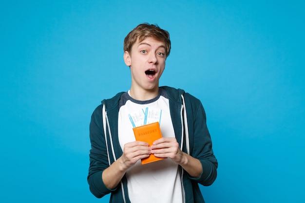Schockierter junger mann in freizeitkleidung, der den mund weit offen hält, reisepass und bordkarte einzeln an der blauen wand hält. menschen aufrichtige emotionen, lifestyle-konzept.