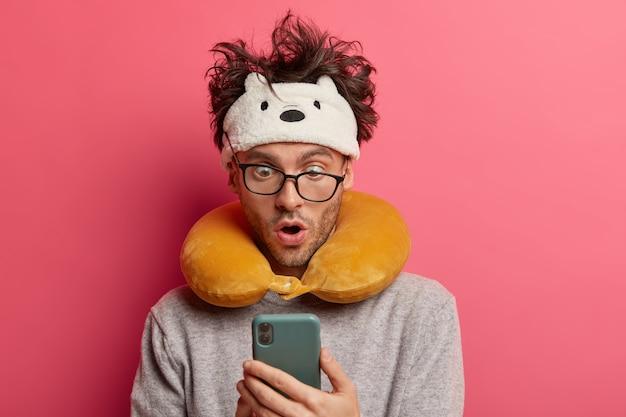 Schockierter junger mann mit unordentlichem haar starrt smartphone an