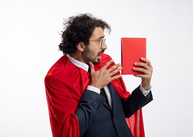 Schockierter junger superheldenmann in der optischen brille, die anzug mit rotem umhang schaut und zeigt auf buch lokalisiert auf weißer wand