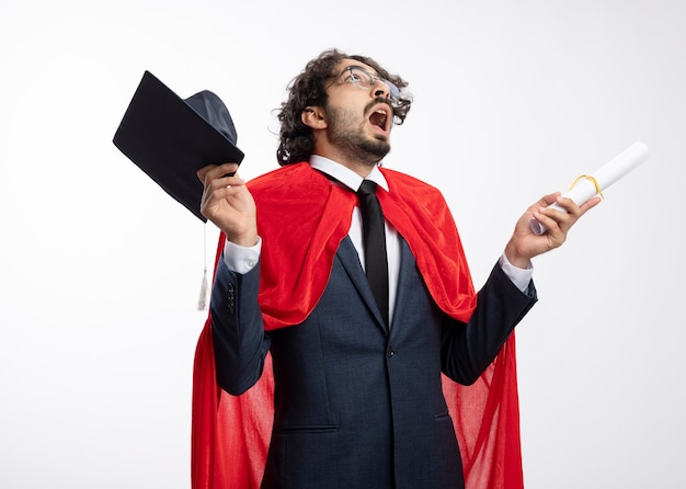 Schockierter junger superheldenmann in der optischen brille, die anzug mit rotem umhang trägt, hält abschlusskappe und diplom lokalisiert auf weißer wand