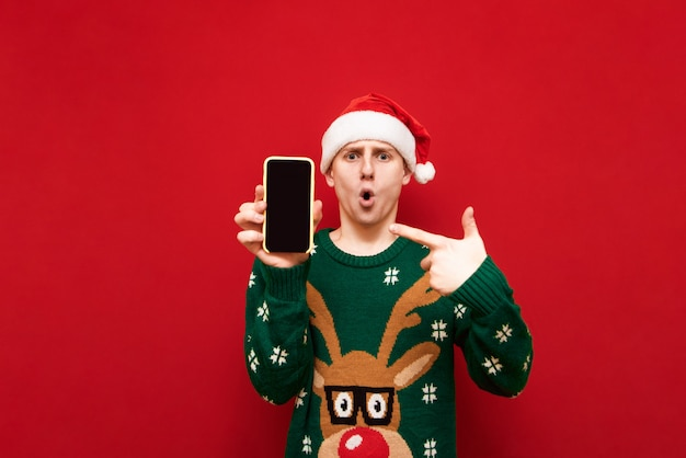 Schockierter kerl in weihnachtsmütze und grünem pullover zeigt seinen finger auf dem smartphone-bildschirm und schaut mit überraschtem gesicht auf rot in die kamera