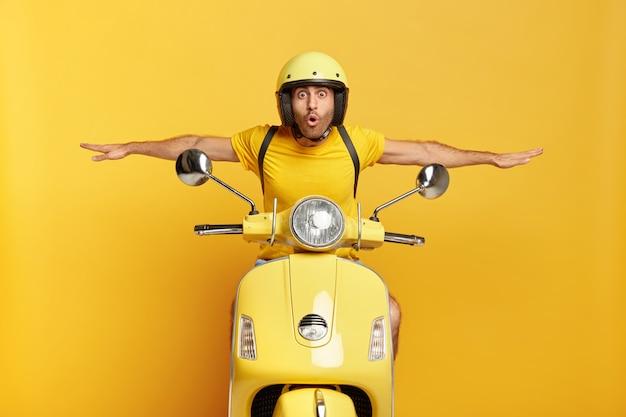 Schockierter kerl mit helm fährt gelben roller