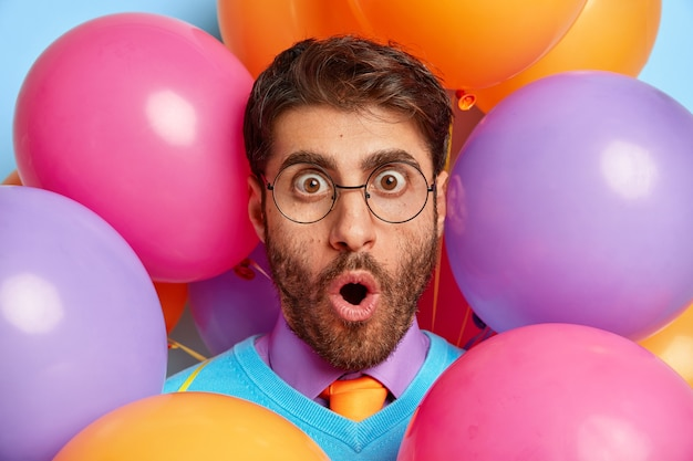 Schockierter kerl, umgeben von partyballons, die aufwerfen
