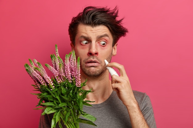 Schockierter kranker mann hält nasentropfen, hat wässrige rote augen, leidet an einer pollenallergie, hat eine entzündung der nase, reagiert auf umweltallergene, hat ein sehr empfindliches immunsystem. heuschnupfen