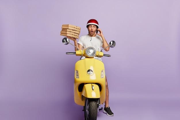 Schockierter lieferbote, der roller fährt, während er pizzaschachteln hält