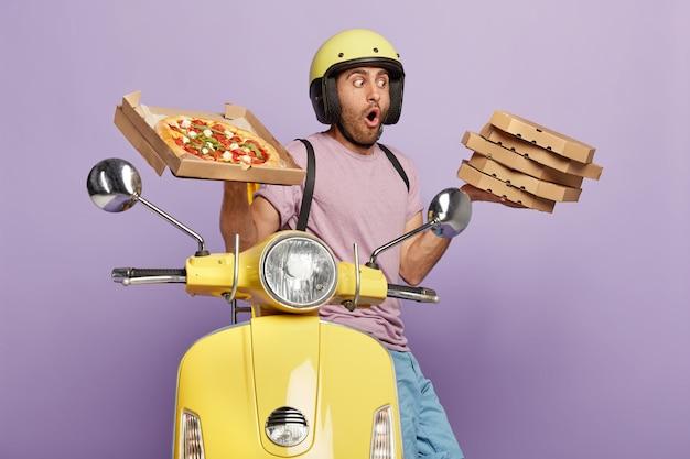 Schockierter lieferbote trägt einen stapel köstlicher italienischer pizza, trägt helm und freizeitkleidung, fährt motorrad, transportiert fast food zum abendessen, isoliert über lila wand. leckerer snack