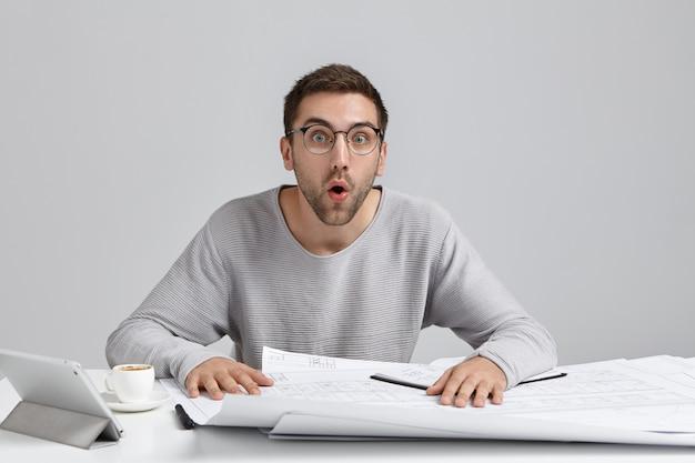Schockierter männlicher ingenieur entwickelt neues bilddesign, sieht mit offenem mund aus und erinnert sich an wichtige treffen