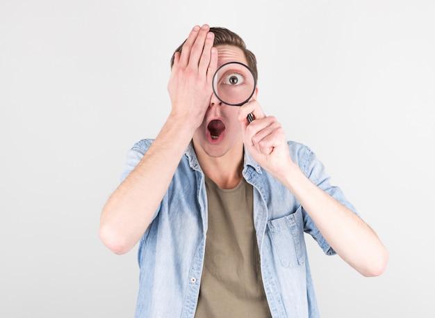 Schockierter mann, der durch eine lupe schaut