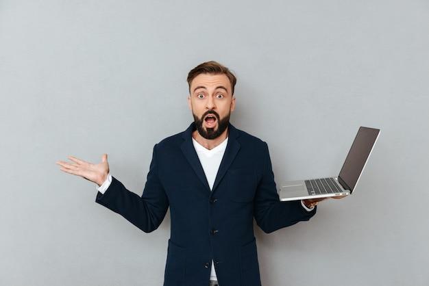 Schockierter mann, der laptop-computer hält und kamera mit geöffnetem mund lokalisiert schaut