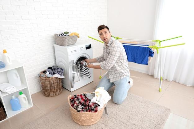 Schockierter mann, der wäsche im badezimmer macht