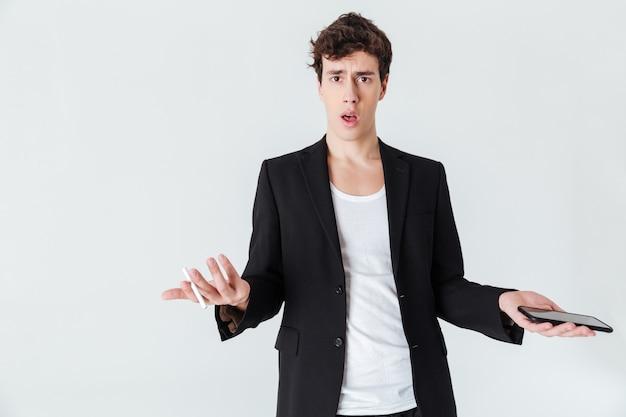 Schockierter mann im anzug, der zigarette und smartphone hält