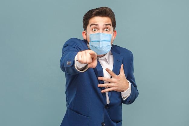 Schockierter mann mit chirurgischer medizinischer maske, der mit schockiertem gesicht mit dem finger auf die kamera zeigt