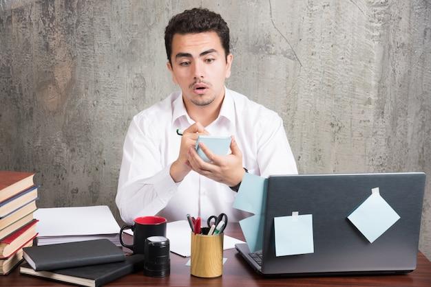 Schockierter mitarbeiter, der am schreibtisch mit dem telefon spielt.