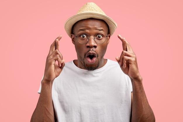 Schockierter schwarzer junger mann mit herausgesprungenen augen, daumen drücken