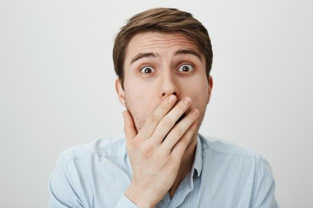 Schockierter sprachloser kerl bedeckt den mund und schnappt erstaunt nach luft