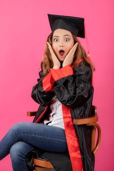 Schockierter student, der ein abschlusskleid trägt und auf einem stuhl sitzt.