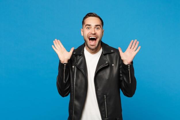 Schockierter stylischer junger bärtiger mann in schwarzer lederjacke, weißem t-shirt, der kamera isoliert auf blauem wandhintergrund studioportrait sieht. menschen aufrichtige emotionen lifestyle-konzept. kopieren sie platz.