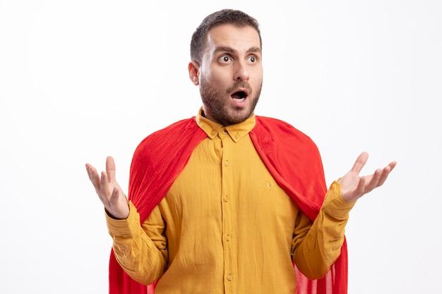 Schockierter superheldenmann mit rotem umhang hält hände offen und betrachtet seite isoliert auf weißer wand