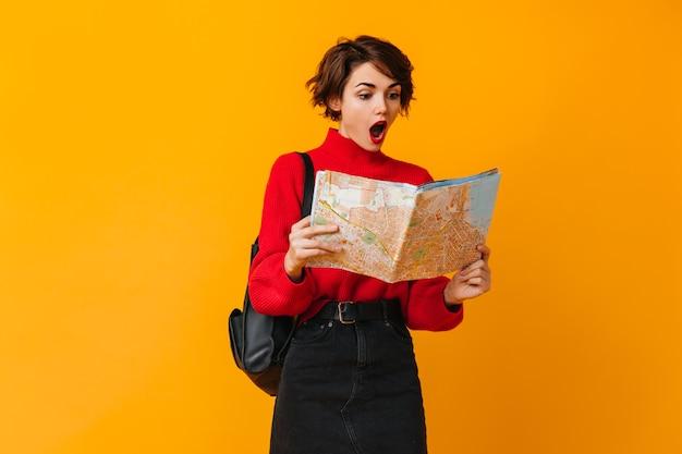 Schockierter tourist, der karte betrachtet