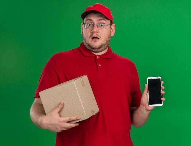 Schockierter übergewichtiger junger lieferbote in optischen gläsern, die pappkarton und telefon lokalisiert auf grüner wand mit kopienraum halten