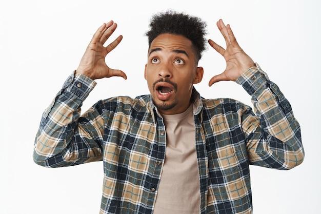 Schockierter und aufgeregter afroamerikaner, der die hände in der nähe des kopfes hält, nach luft schnappt und in ehrfurcht auf den fernseher starrt, überwältigende informationen, auf atemberaubende nachrichten auf weiß starren