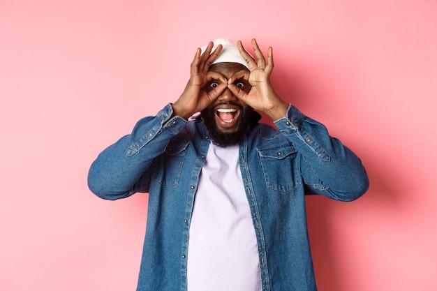 Schockierter und beeindruckter afroamerikaner, der durch ein handfernglas in die kamera starrt, eine erstaunliche promo sieht und über rosafarbenem hintergrund steht