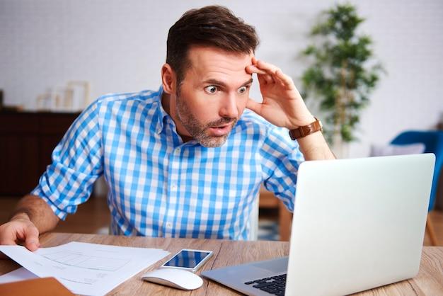 Schockierter und besorgter mann, der in seinem büro arbeitet
