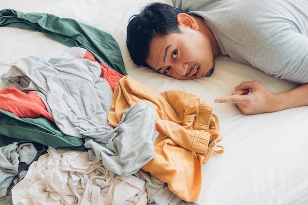 Schockierter und trauriger mann, der sich um den ganzen haufen kleider kümmern muss.