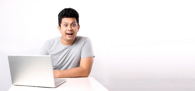 Schockierter und überraschter asiatischer mann, der die computerseite hat. mit kopierplatz.