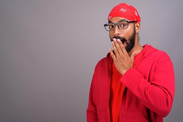 Schockierter und überraschter inder, der rotes hemd trägt