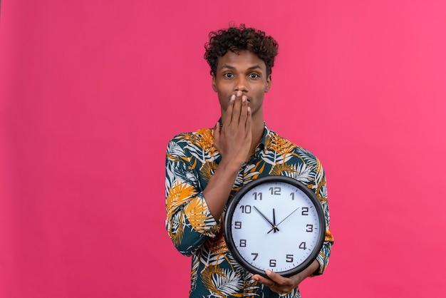 Schockierter und verwirrter junger dunkelhäutiger mann mit dem lockigen haar im bedruckten blatthemd, das wanduhr hält, die zeit mit den händen zeigt, die mund auf einem rosa hintergrund bedecken