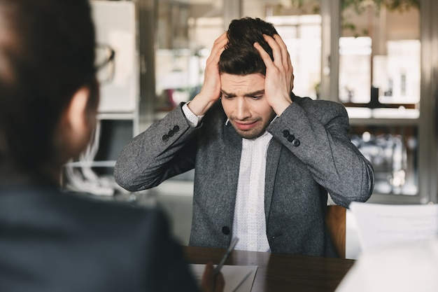 Schockierter verärgerter mann der 30er jahre, der sich während eines vorstellungsgesprächs im büro sorgen macht und sich den kopf schnappt, mit einem kollektiv von spezialisten - geschäfts-, karriere- und rekrutierungskonzept