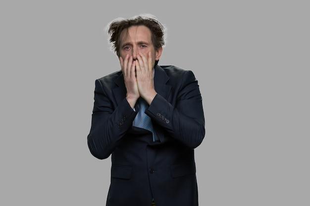 Schockierter verzweifelter geschäftsmann, der sein gesicht bedeckt. gestresster überforderter mann im anzug vor grauem hintergrund. es ist ein fehlschlag.
