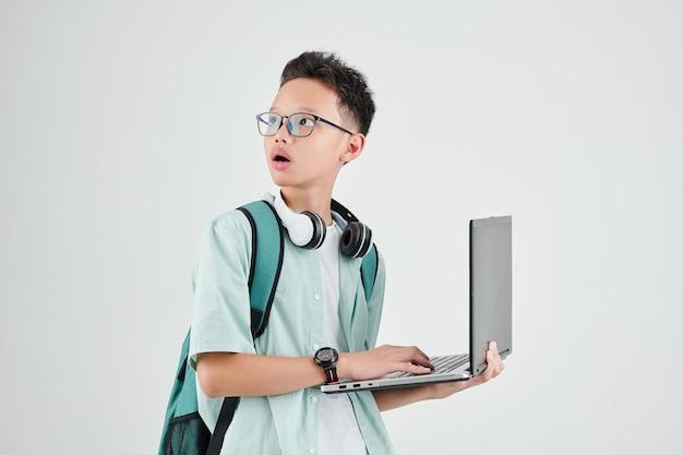 Schockierter vietnamesischer schüler mit laptop, der sich umdreht und motuh öffnet