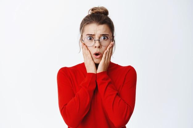 Schockierter weiblicher ceo-manager, der besorgt und besorgt aussieht, die hände im gesicht hält und verängstigt nach vorne starrt, eine brille trägt, weiße wand