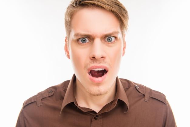 Schockierter wütender junger mann mit geöffnetem mund