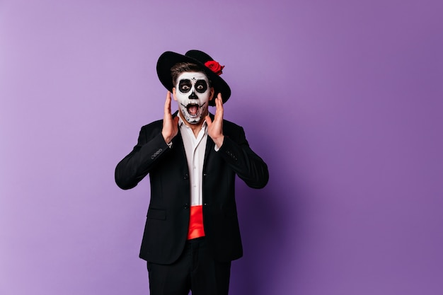 Schockierter zombiemann in eleganter kleidung, die auf lila hintergrund in halloween aufwirft. überraschter kerl im mexikanischen outfit, der tag der toten feiert.