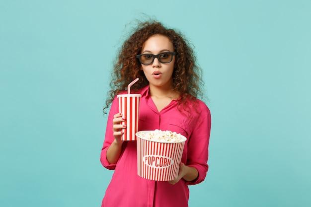 Schockiertes afrikanisches mädchen in 3d-imax-brille, das filmfilm hält, hält popcorn, tasse soda einzeln auf blau-türkisem hintergrund im studio. menschen emotionen im kino, lifestyle-konzept. kopieren sie platz.