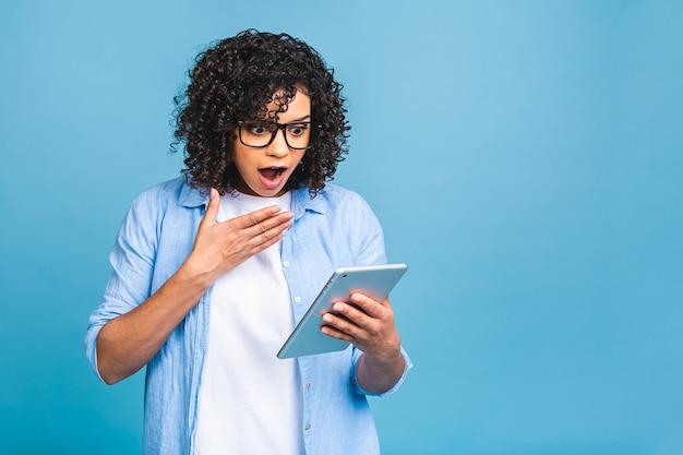 Schockiertes amerikanisches studentenmädchen mit dem gelockten afrikanischen haar, das digitales tablett über lokalisiertem blauem hintergrund mit kopienraum für text, logo oder werbung hält.