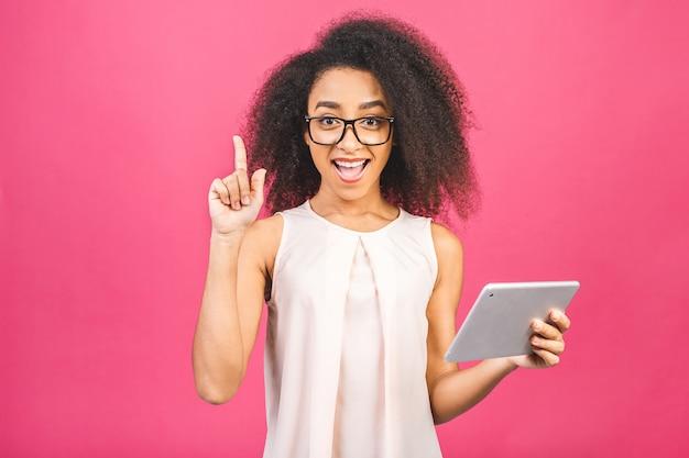 Schockiertes amerikanisches studentenmädchen mit dem gelockten afrikanischen haar, das digitales tablett über rosa mit kopienraum für text, logo oder werbung hält.