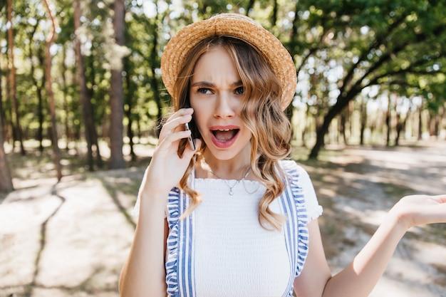 Schockiertes blondes mädchen, das im park steht und am telefon spricht. außenaufnahme der schönen jungen frau im hut, die erstaunen während des gesprächs ausdrückt.