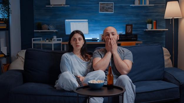 Schockiertes, erstauntes junges paar, das sich eine dokumentarsendung im fernsehen anschaut