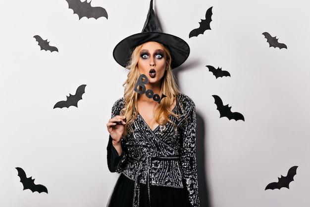 Schockiertes europäisches mädchen im halloween-kostüm. entzückende junge hexe in der schwarzen kleidung, die mit fledermäusen aufwirft.