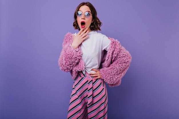 Schockiertes europäisches mädchen im weißen t-shirt und im rosa pelzmantel, der aufwirft. innenfoto der hübschen frau mit der kurzen frisur, die erstaunen auf lila wand ausdrückt.