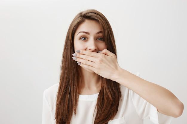 Schockiertes fröhliches mädchen bedeckt mund mit handfläche, hält sich vom reden auf