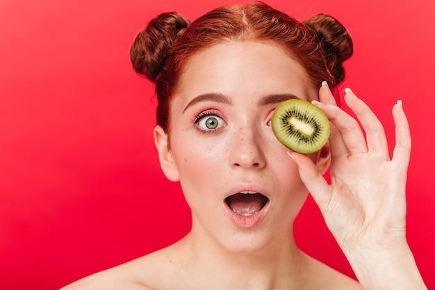 Schockiertes ingwermädchen, das kiwi hält. studioaufnahme der überraschten frau mit exotischer frucht lokalisiert auf rotem hintergrund.
